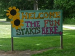 "Photo of a hand painted sign reading ""Welcome The Fun Starts Here"""
